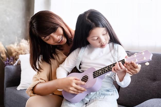 Мать учит дочь играть на укукеле, вместе заниматься спортом, отдыхать в гостиной, размытый свет вокруг