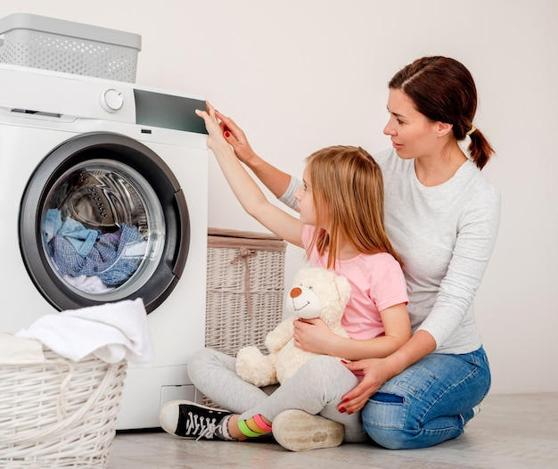 Mother teaching daughter how to operate washing machine in light bathroom