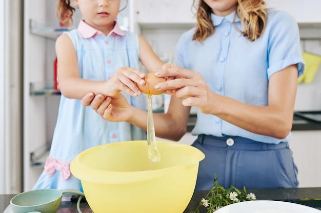 Мать учит дочь, как разбивать яйца в миске при приготовлении теста для печенья