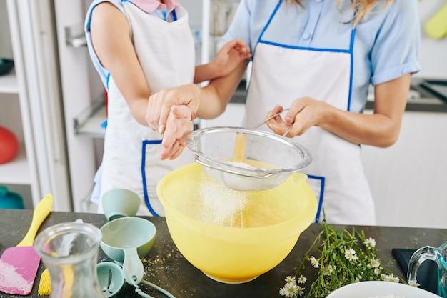 ペストリーやピザの生地を作るときにふるいを使ってボウルに小麦粉をふるいにかける方法を娘に教える母