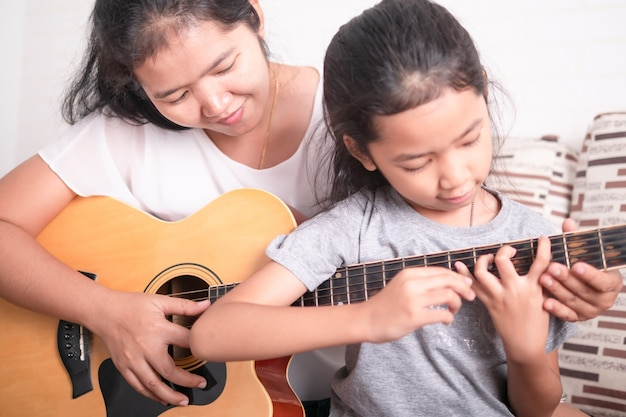 Mother teaching daughter to play guitar.