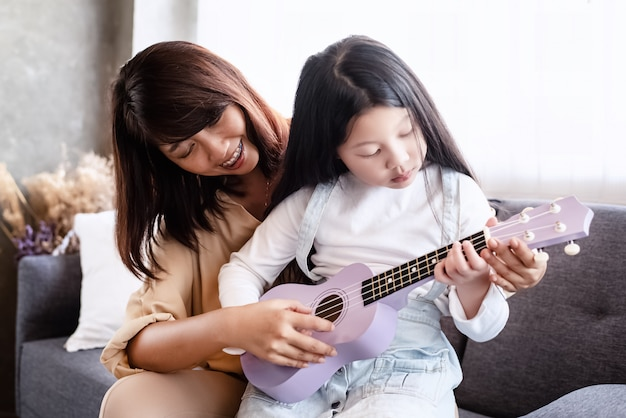 Mother teaching daughter for playing ukukele,doing activity together,relax time,at living room,blurry light around