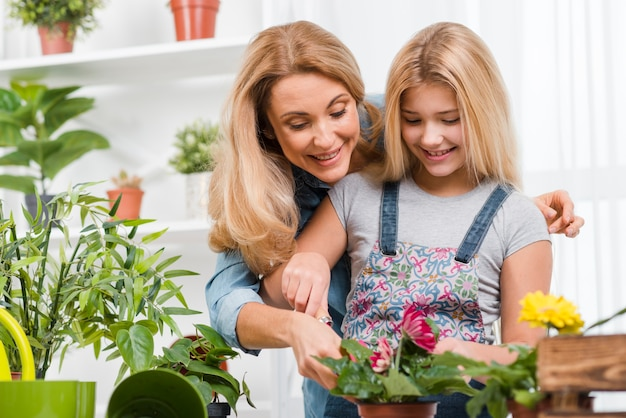 Mother teaching girl to plant flowers