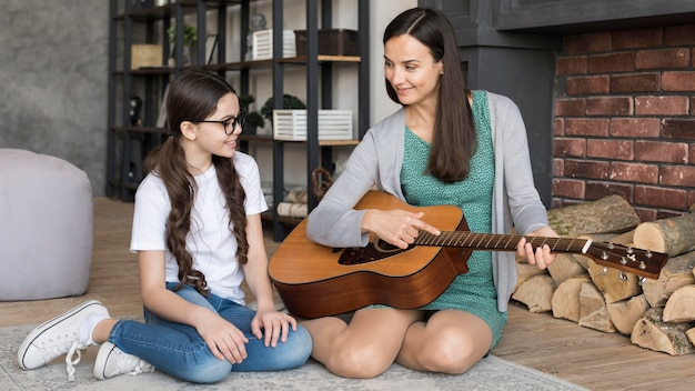 Mother teaching girl to play guitar