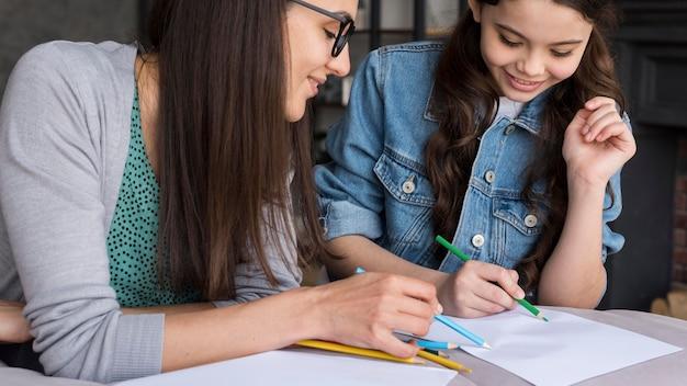 描画する女の子を教える母親