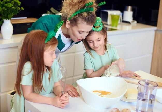 컵케익을 굽는 방법을 아이들에게 가르치는 어머니