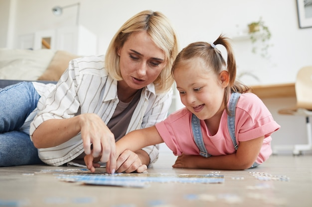 Mother teaching her daughter with down syndrome collecting puzzles they lying on the floor in the room