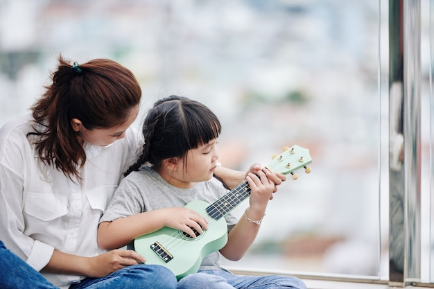 Mother teaching her little daughter how to play ukulele and showing her chords
