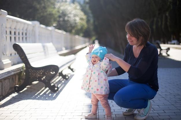 1歳の娘に屋外での歩き方を教える母親