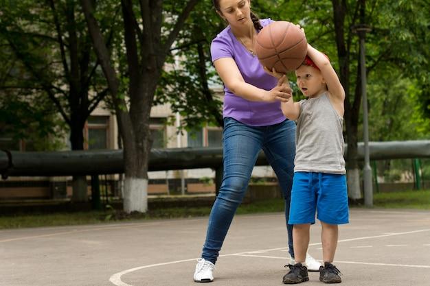 母は息子にバスケットボールをするように教えている
