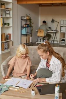 居間のテーブルに座って描くように幼い息子に教える母親