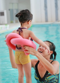 Mother teaching kid in swimming pool with foam noodle