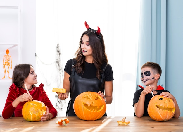 Mother teaching kids how to carve pumpkins
