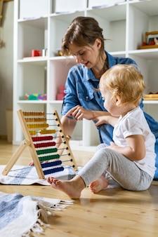 Мать учит маленького ребенка, рассчитывая на разноцветные детские деревянные экологические счеты на полу