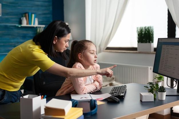 Мать учит маленького ученика о школьном уроке дома