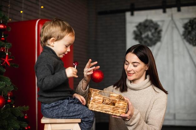 Madre che insegna al figlio come decorare l'albero di natale