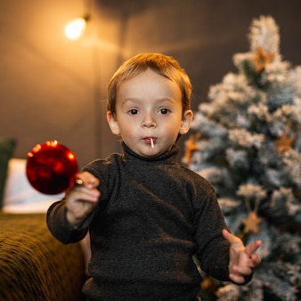 Mother teaching son how to decorate christmas tree