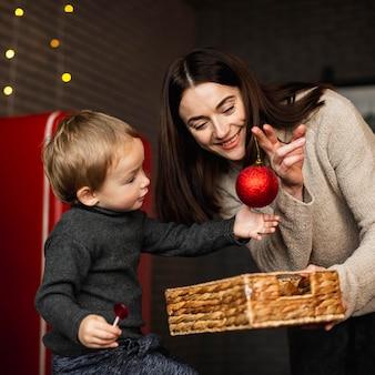 Мать учит сына украшать елку