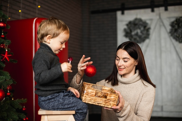 クリスマスツリーを飾る方法を息子に教える母