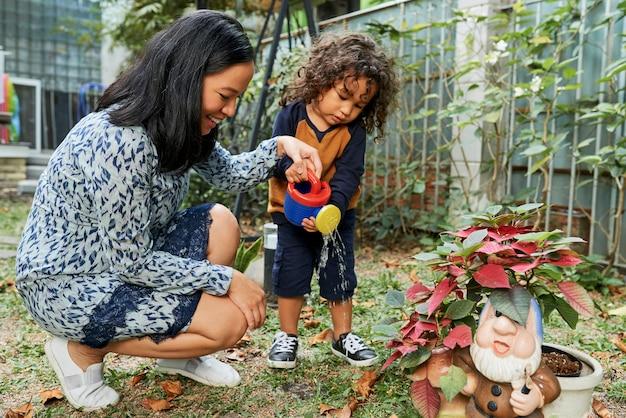 아들에게 식물에 물주는 법을 가르치는 어머니