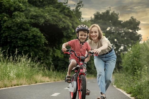 Мать учит сына кататься на велосипеде. счастливый милый мальчик в шлеме учится кататься на велосипеде по велосипедной дорожке в летний дождливый день во время заката. выходные с семьей.