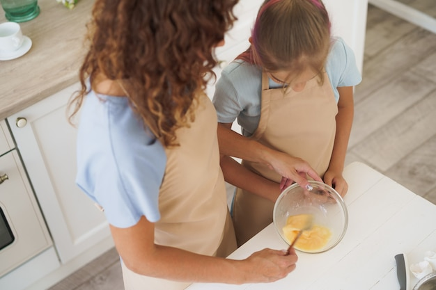 Mother and teen daughter making dough for pastry toghether in kitchen