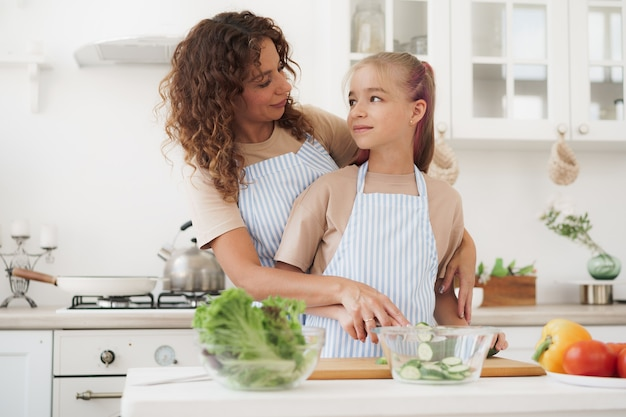 Mother and teen daughter preparing vegetable salad at kitchen