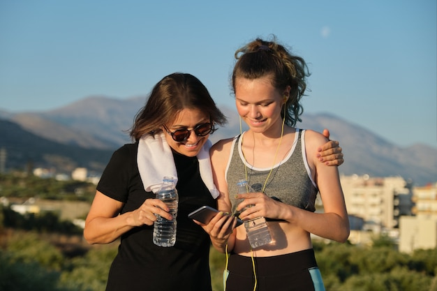 Mother and teenage daughter drinking water on hot summer day after exercise and jogging outdoors in mountains