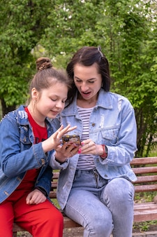 Mother and teenage daughter walking in a park, sitting on a bench and looking in smartphone, happy young caucasian woman with long hair and teenage girl surfing the internet outdoors, lifestyle family
