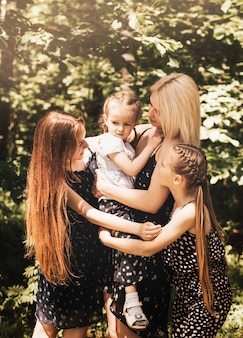 A mother and three daughters cuddle in the summer in nature. large family. spending time outdoors, happy family life