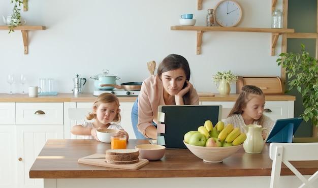 テーブルでノートパソコンを操作し、キッチンで電話で商談をしながら、娘の世話をする母親。母親は、家族が自己隔離している間、リモートで働いています。