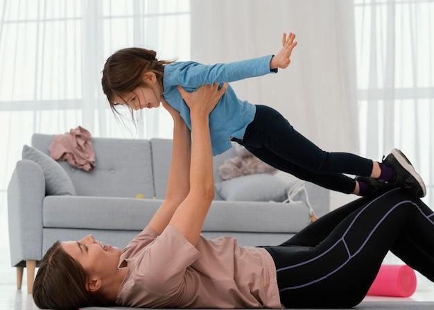 屋内で子供と一緒に母親のトレーニング