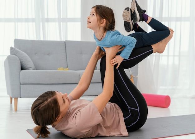 マットの上で子供と一緒に母親のトレーニング