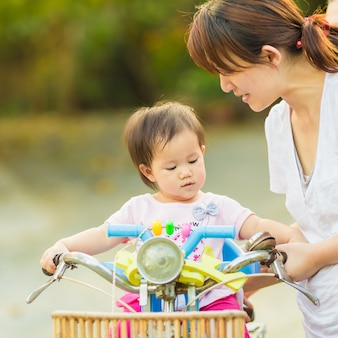 Mother try to ride a bicycle with her baby