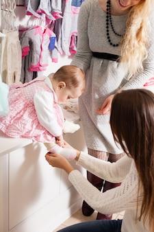衣料品店で幼い娘の靴下を履こうとしている母親