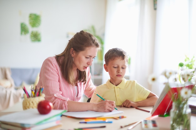 Mother tutor helps son to do lessons. correct the error in home lessons.