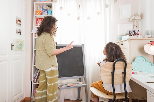Mother tutoring girl at home