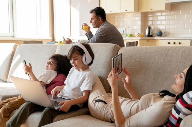 Mother and twins using different devices at home