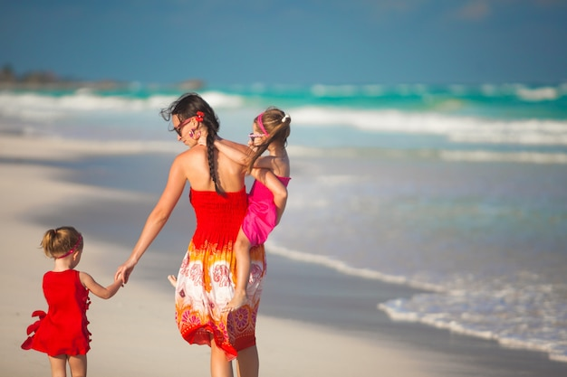 Mother and two adorable daughters walking at exotic beach on sunny day