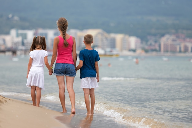 Mother and two children son and daughter walking together on sand beach in sea water in summer with bare feet in warm ocean waves.