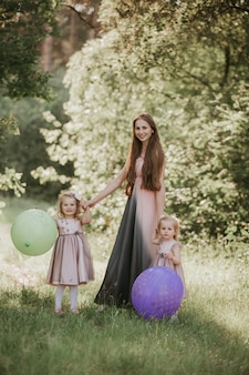 Mother and two daughter having fun in the park. happy family concept. beauty nature scene with family outdoor lifestyle. happy family resting together. happiness and harmony in family life.