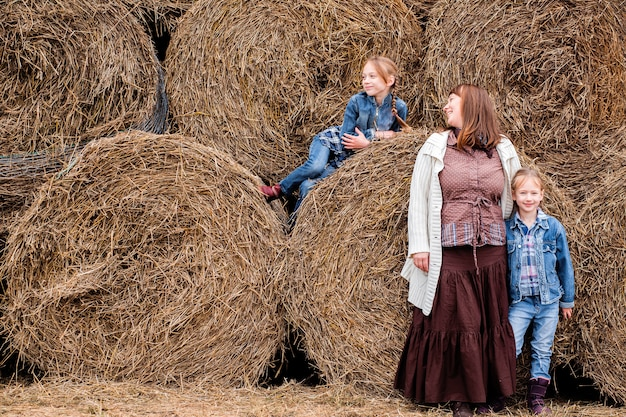 The mother and two daughters are resting near the hay