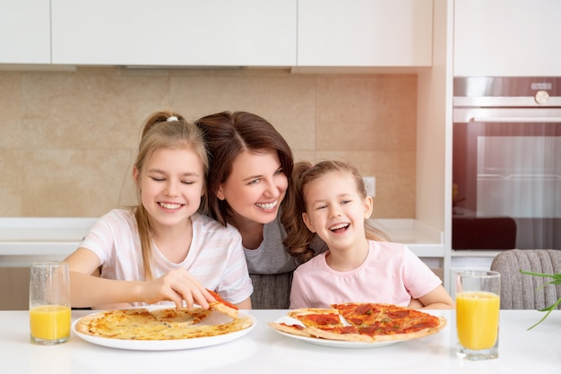 Mother and two daughters eating homemade pizza at a table in kitchen, happy family concept