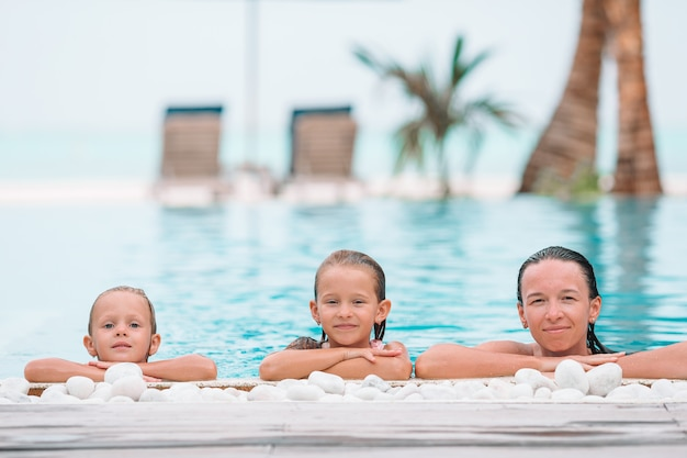 Mother and two kids enjoying summer vacation in luxury swimming pool