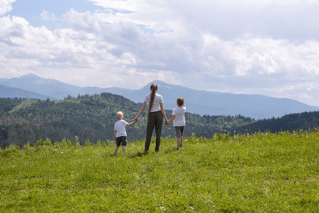 Mother and two little sons stand holding hands on a green field