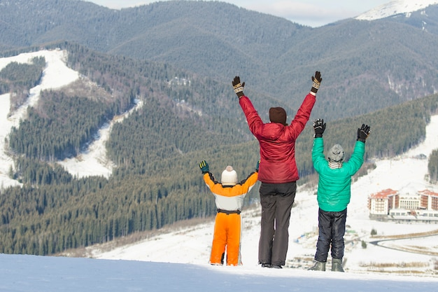 Mother and two sons are raising their hands on snow-capped mountains.