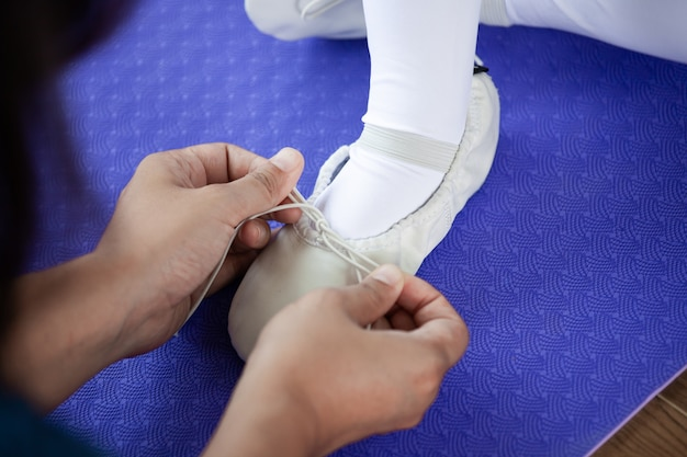 Mother tying feet pointe shoes to her daughter preparing for practicing a ballet