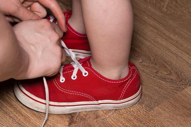 그의 아들의 신발 끈을 묶는 어머니.
