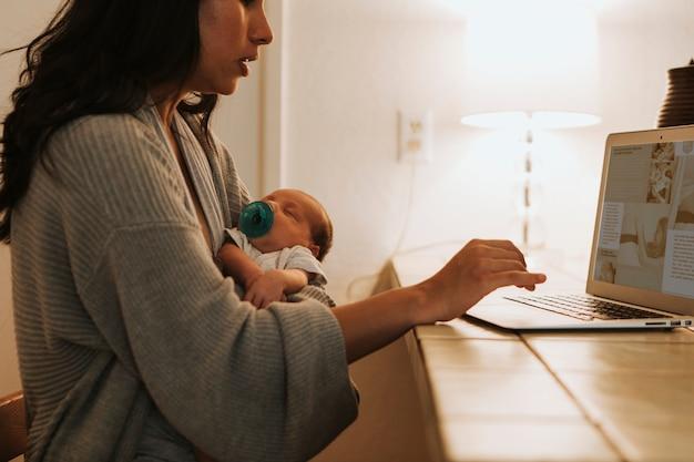 어머니는 컴퓨터를 사용 하 고 그녀의 아기를 잡고