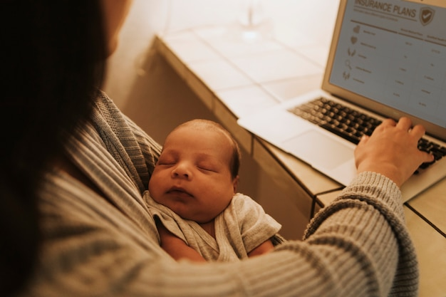 Mother using a computer and holding her baby